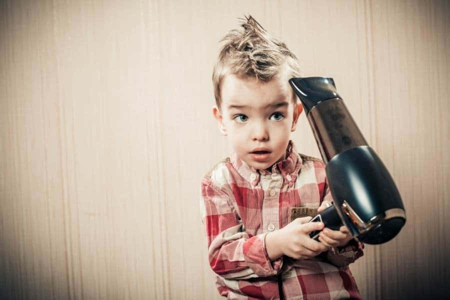child with hairdryer