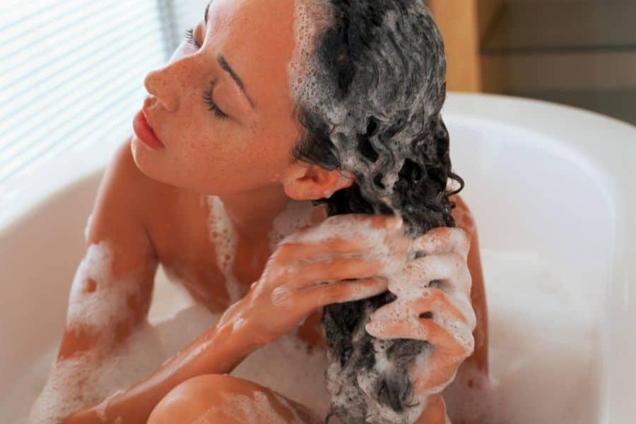 woman chelating hair in bathtub